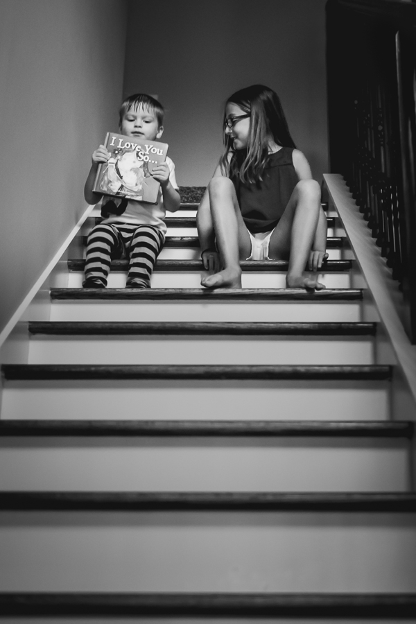 Brother and sister bumping down the stairs in black and white.