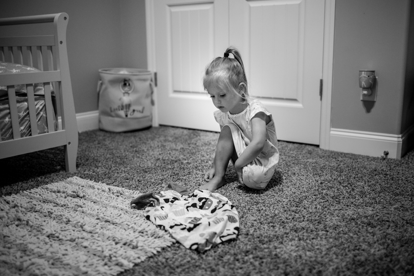 Little girl preparing to put on a dress