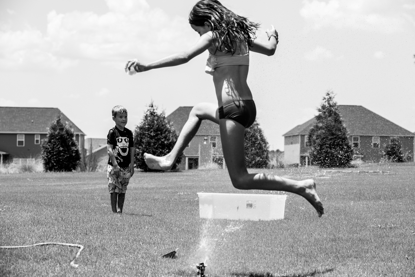 Girl running through a sprinkler while her brother watches